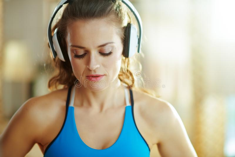 Vrouw die aan muziek met hoofdtelefoons in modern huis luistert stock foto