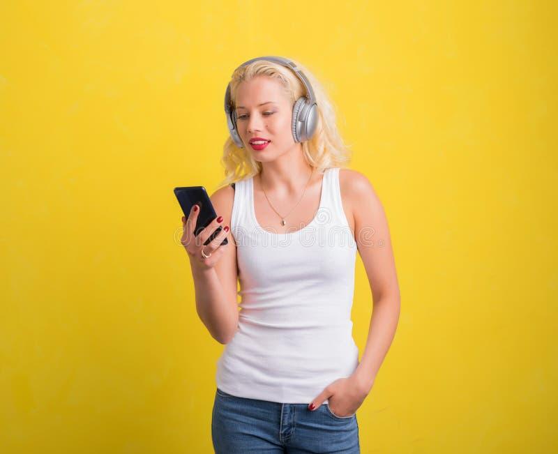 Vrouw die aan muziek op hoofdtelefoon van haar telefoon luisteren royalty-vrije stock foto's