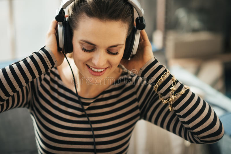 Vrouw die aan muziek in zolderflat luisteren Sluit omhoog portret stock foto