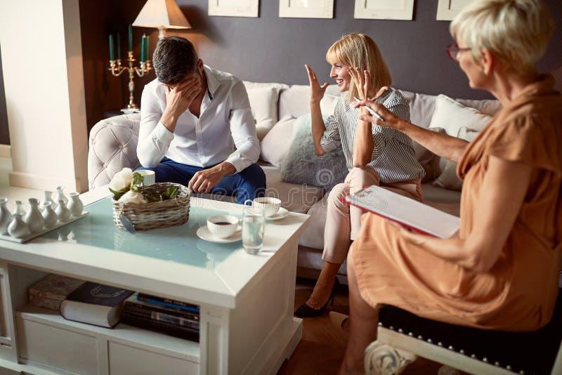 Vrouw die aan psycholoog echtelijk conflict met echtgenoot verklaren stock foto