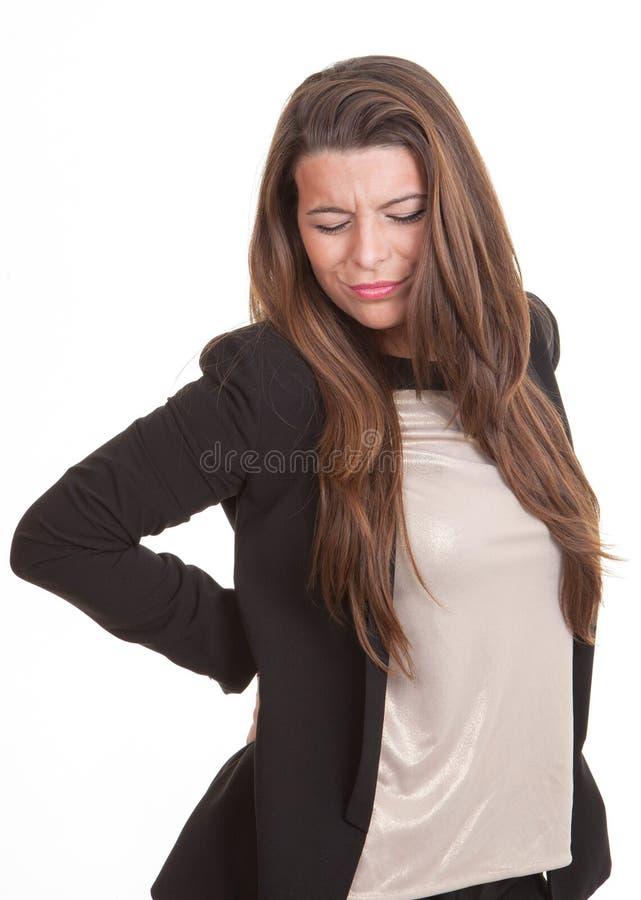 Vrouw die aan rugpijn of pijn lijden stock fotografie