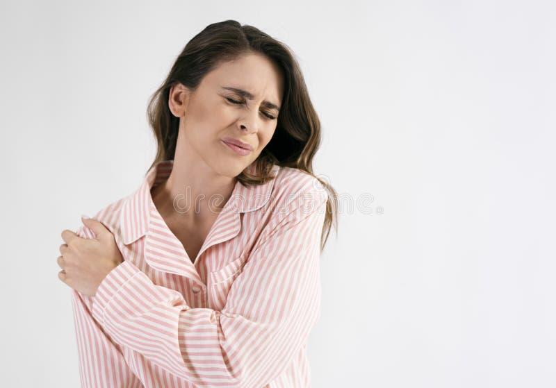 Vrouw die aan schouderpijn lijdt stock fotografie