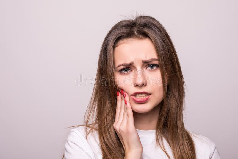 Vrouw die die aan tandpijn, tandbederf of gevoeligheid lijden op grijs wordt geïsoleerd stock afbeeldingen
