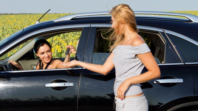 Vrouw die aan vrouwelijke bestuurder in auto spreekt stock afbeeldingen