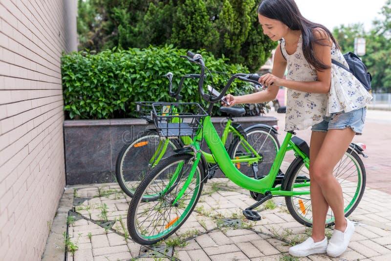 Vrouw die aandeelfiets in de stad met behulp van stock fotografie