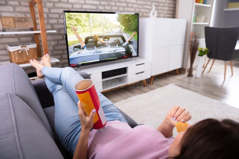 Vrouw die Aardappel Chips While Watching Television eten stock afbeeldingen