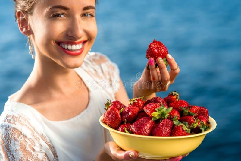 Vrouw die Aardbei eten stock afbeelding