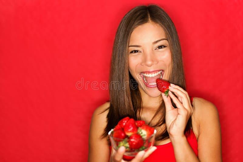 Vrouw die aardbeien eet royalty-vrije stock afbeeldingen