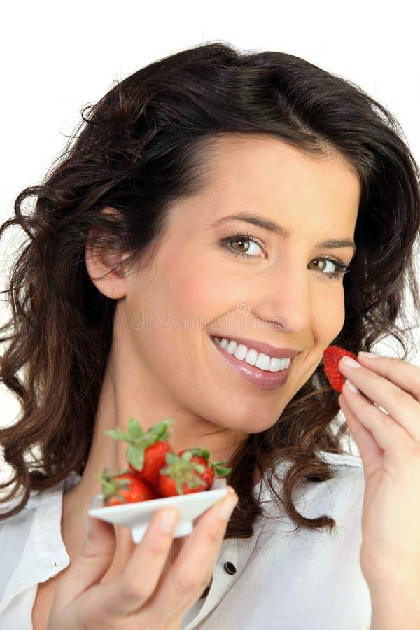 Vrouw die aardbeien eet stock foto