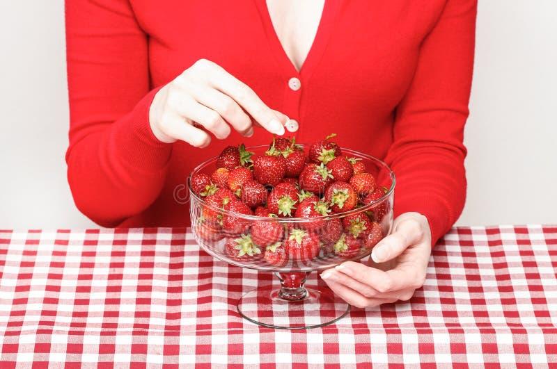 Vrouw die aardbeien eten stock afbeelding