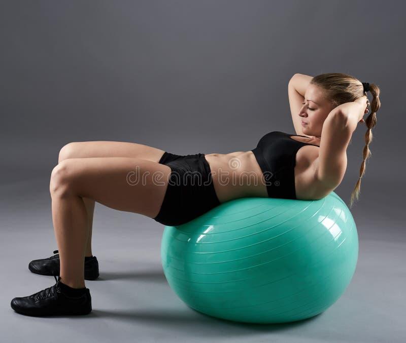 Vrouw die abs op gymnastiekbal doen royalty-vrije stock foto