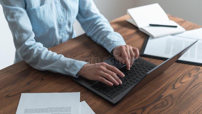 Vrouw die achter houten lijst in bureau werken stock fotografie