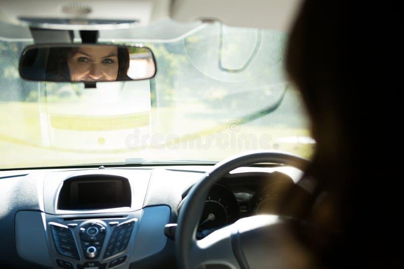 Vrouw die achteruitkijkspiegel onderzoeken terwijl het drijven van een auto royalty-vrije stock fotografie