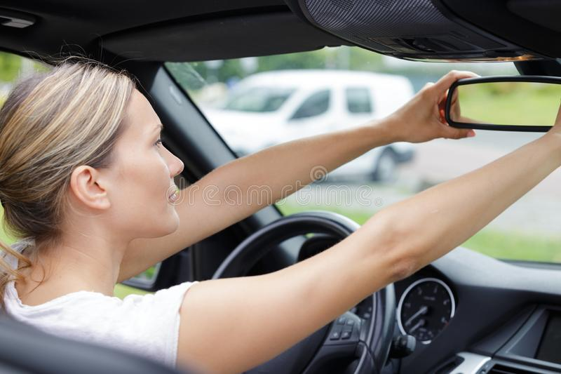 Vrouw die in achteruitkijkspiegelauto kijken stock foto's