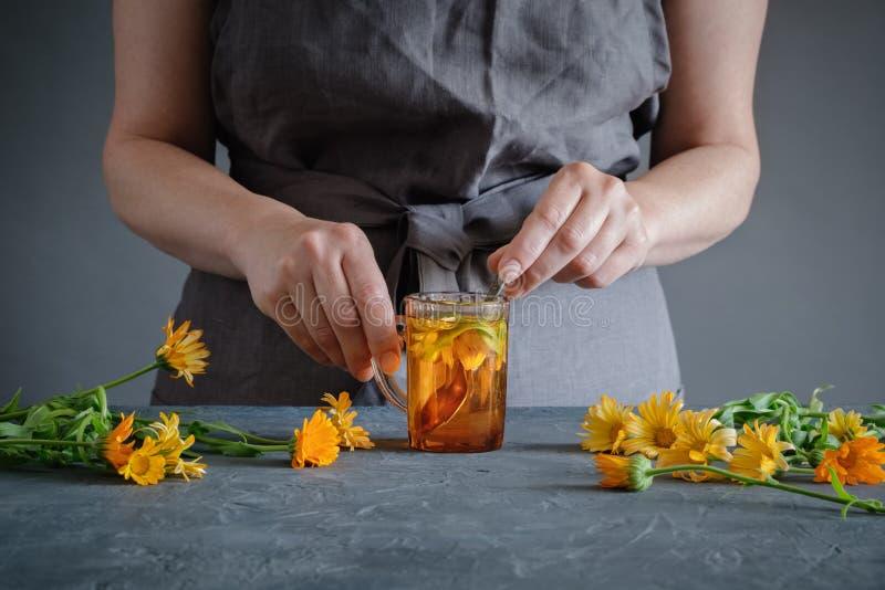 Vrouw die aftreksel met calendula of goudsbloembloemen maken stock foto's
