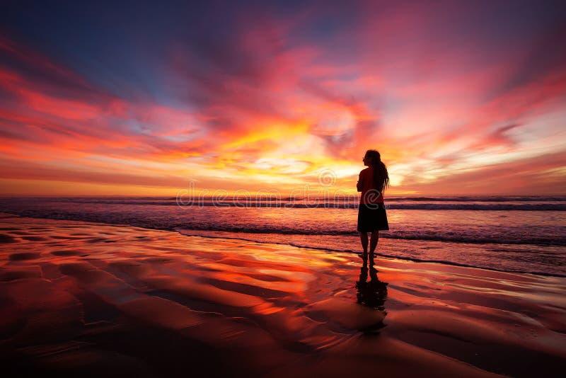 Vrouw die alleen op het strand in de zonsondergang lopen stock afbeeldingen