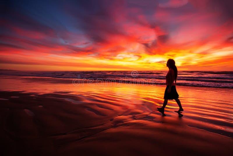 Vrouw die alleen op het strand in de zonsondergang lopen royalty-vrije stock afbeeldingen