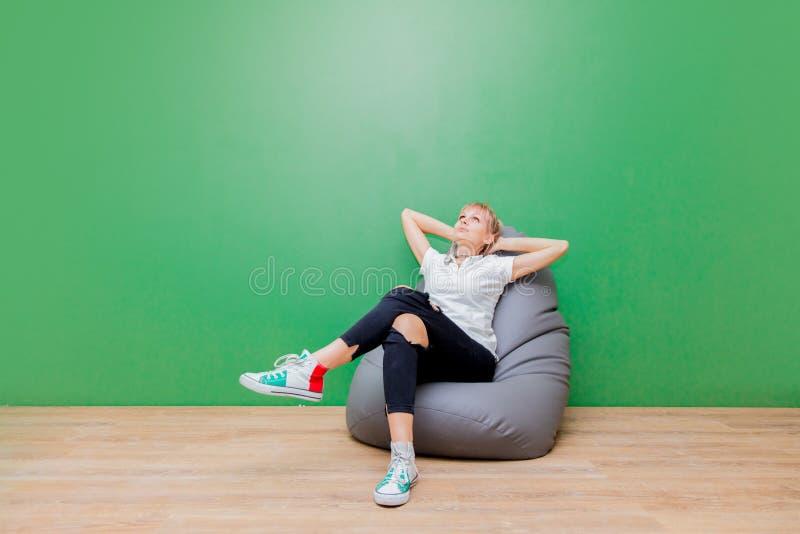 Vrouw die als voorzitter na zich het bewegen aan een nieuwe flat rusten stock fotografie