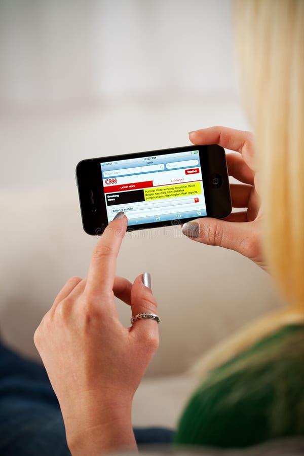 Vrouw die Apple-iPhone 4 gebruiken om Nieuwsplaats te doorbladeren royalty-vrije stock afbeelding