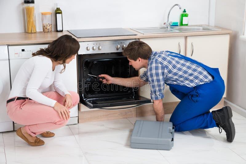 Vrouw die Arbeider bekijken die Oven herstellen royalty-vrije stock foto