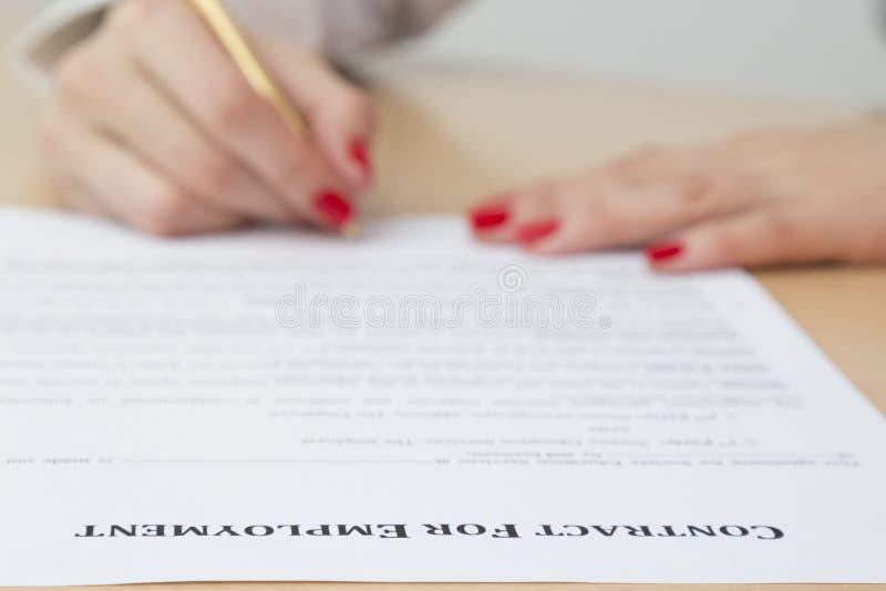 Vrouw die arbeidsovereenkomst ondertekenen stock foto's