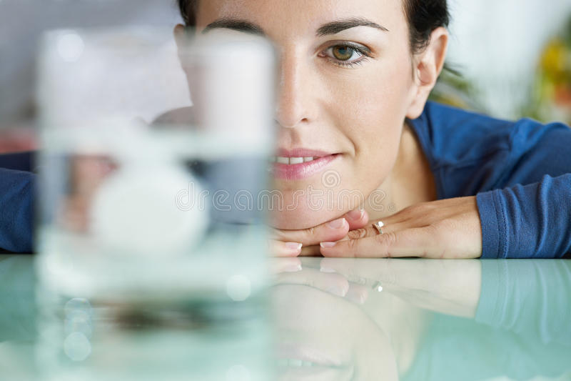 Vrouw die aspirine in glas water bekijkt stock foto's