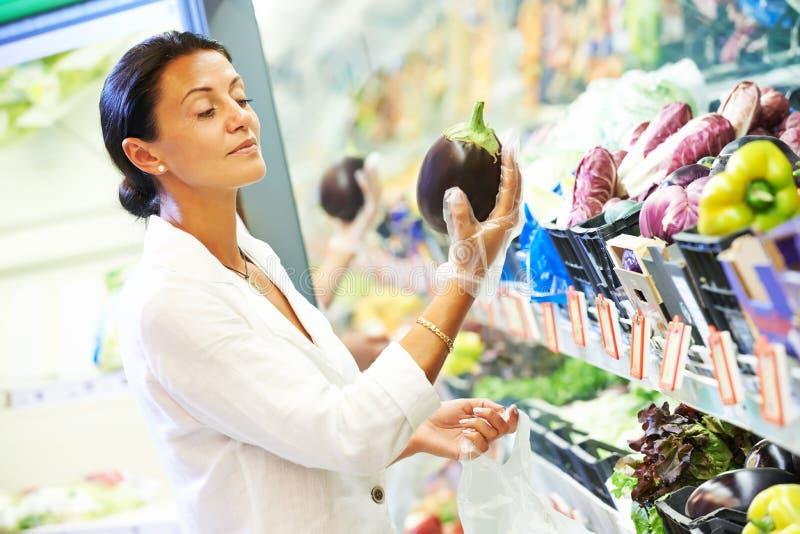 Vrouw die aubergine kiezen Het plantaardige winkelen in supermarkt stock afbeeldingen