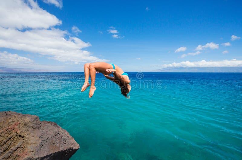 Vrouw die backflip in oceaan doen royalty-vrije stock afbeelding