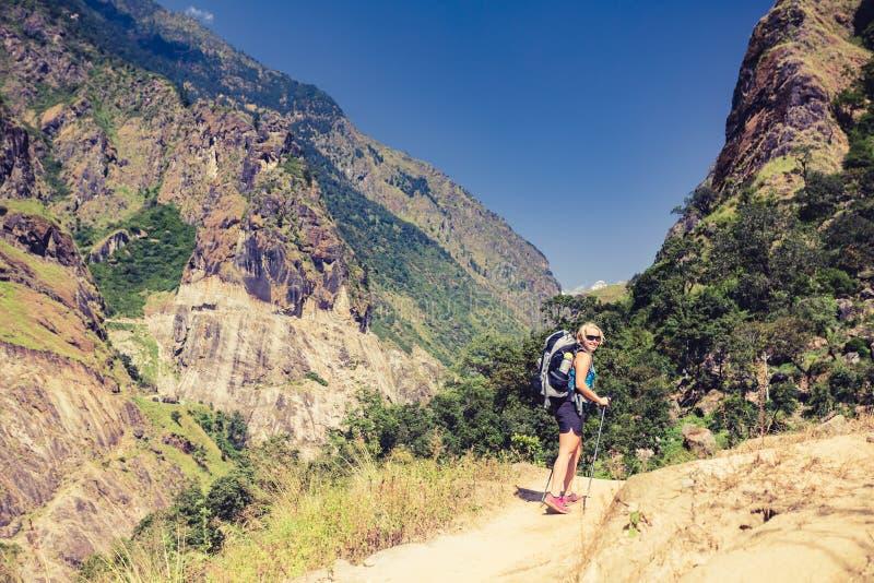 Vrouw die backpacker met rugzak in Himalayagebergte, Nepal beklimmen stock afbeeldingen