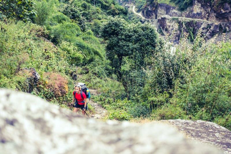 Vrouw die backpacker met rugzak in Himalayagebergte, Nepal beklimmen royalty-vrije stock foto's