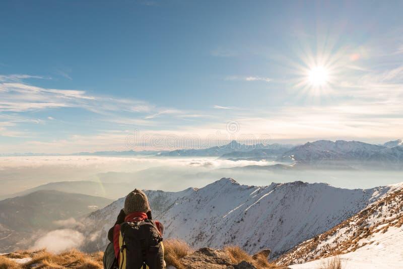 Vrouw die backpacker op bergbovenkant rusten Achtermening, de winterlevensstijl, koud gevoel, zonster in backlight royalty-vrije stock fotografie