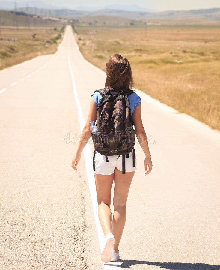 Vrouw die backpacker op weg lopen royalty-vrije stock afbeeldingen