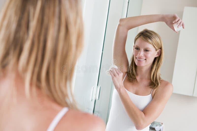 Vrouw die in badkamers deodorant toepast royalty-vrije stock foto