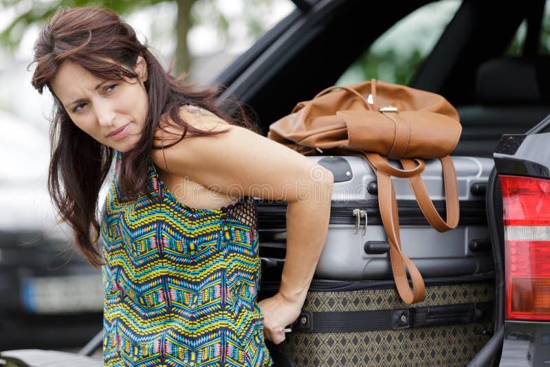 Vrouw die bagage in autolaars proberen te drukken stock foto's