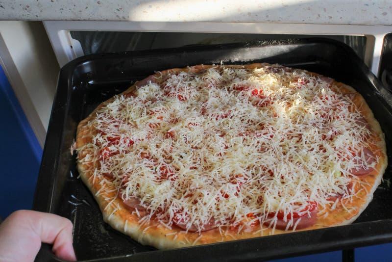 Vrouw die bakselblad met pizza in oven zetten royalty-vrije stock foto