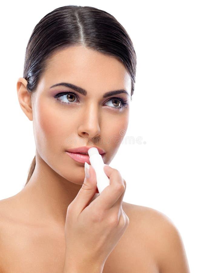Vrouw die balsem op lippen toepassen stock afbeeldingen
