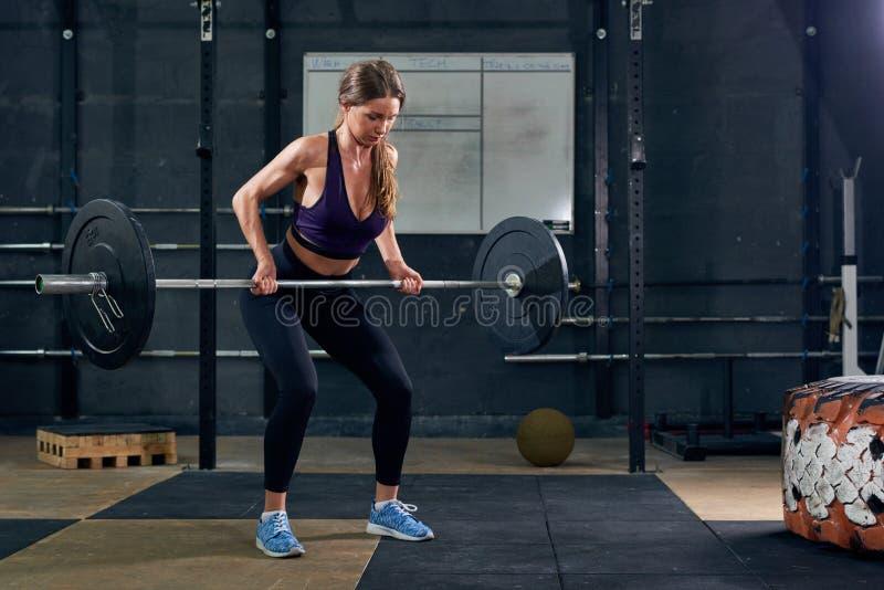 Vrouw die Barbell in Gymnastiek opheffen stock afbeelding