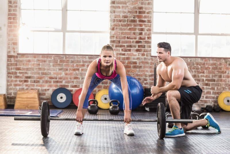 Vrouw die barbell met haar trainer bij crossfitzitting opheffen stock foto's