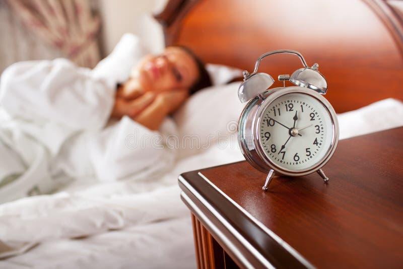 Vrouw die in bed hand uitbreiden tot wekker stock foto