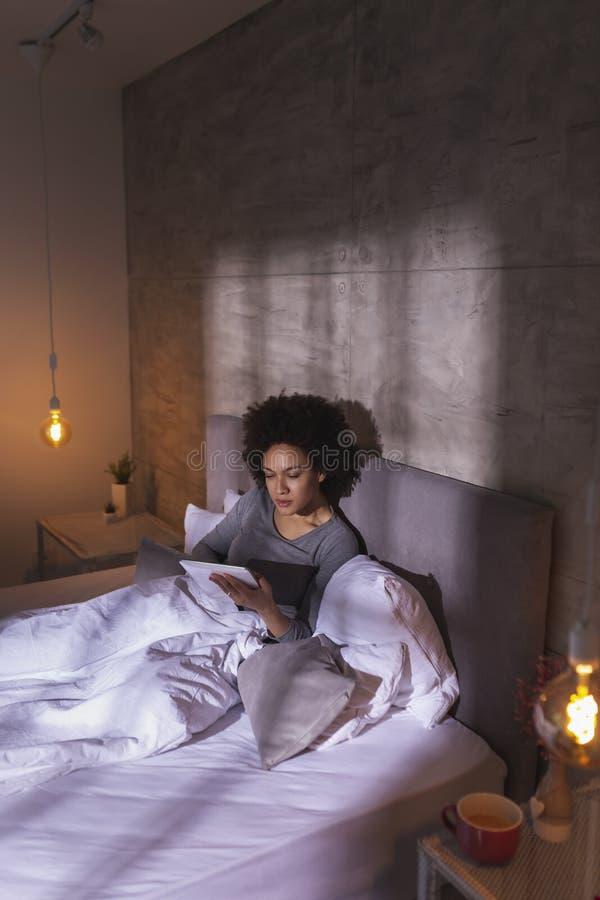 Vrouw die in bed liggen en het net surfen royalty-vrije stock afbeeldingen