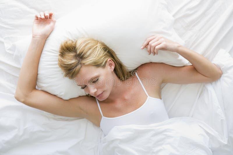 Vrouw die in bed ligt royalty-vrije stock afbeeldingen