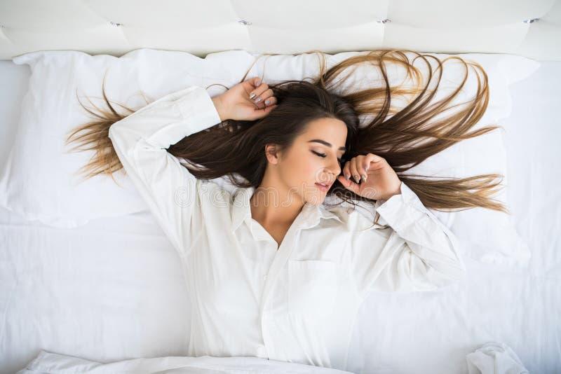 Vrouw die in bed met handen naast haar hoofd op het hoofdkussen rusten royalty-vrije stock foto's
