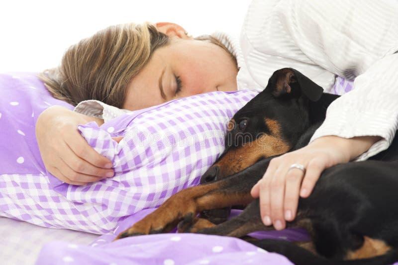 Vrouw die in bed met hond liggen royalty-vrije stock foto's