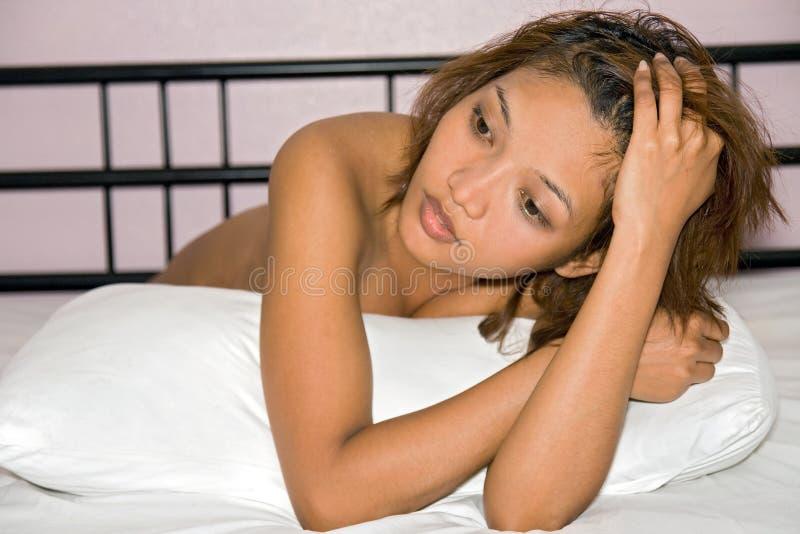 Vrouw die in bed rusten stock afbeeldingen