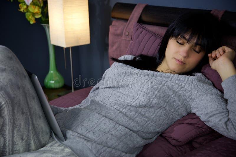 Vrouw die in bed rusten terwijl het spelen met tablet middelgroot schot stock afbeelding
