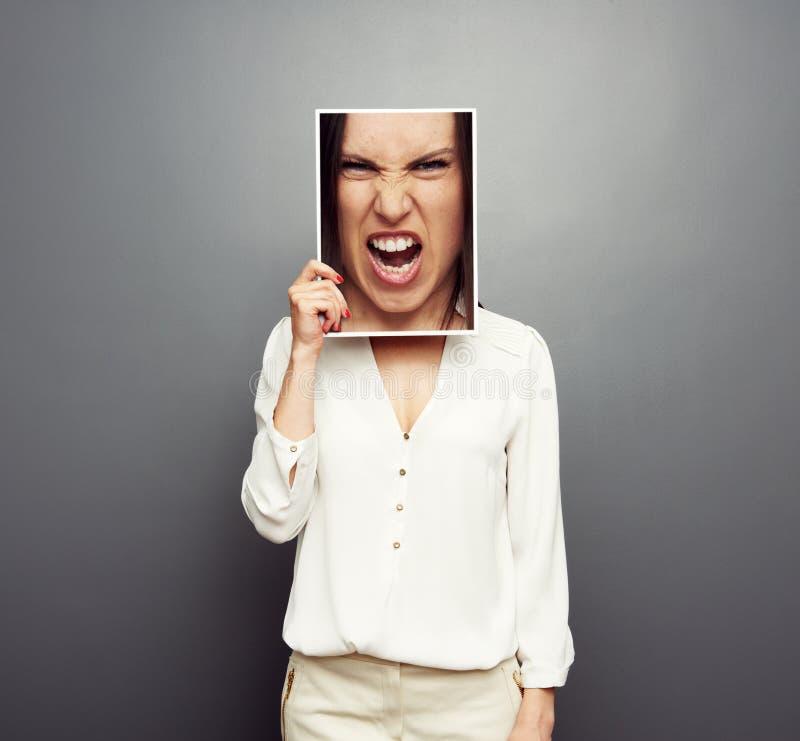 Vrouw die beeld behandelen met groot boos gezicht stock afbeelding