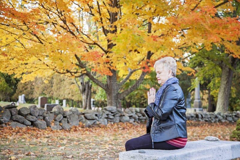Vrouw die in begraafplaats bidt royalty-vrije stock afbeeldingen