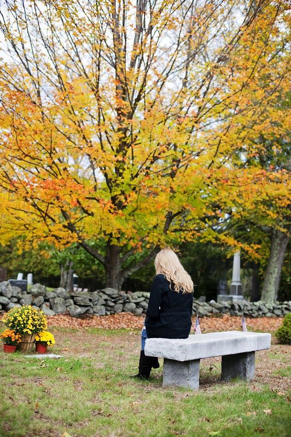 Vrouw die in begraafplaats rouwt stock afbeelding