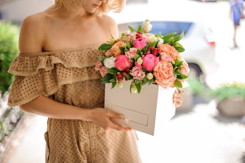Vrouw die in beige kleding een vierkante die doos houden met heldere flo wordt gevuld stock afbeelding