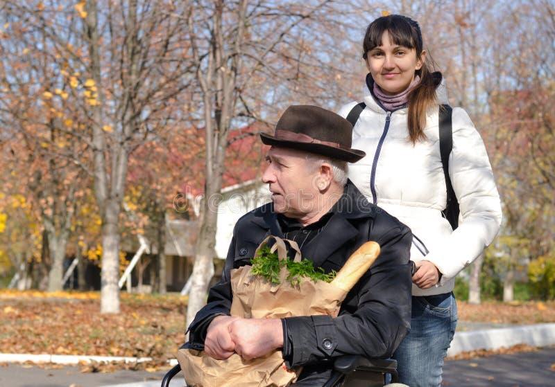 Vrouw die bejaarden het gehandicapte man winkelen nemen royalty-vrije stock fotografie
